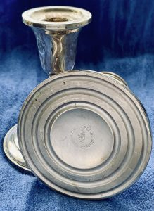 Image of a matching set of short silver candlesticks, one on its side revealing the Sterling stamp and weighted component